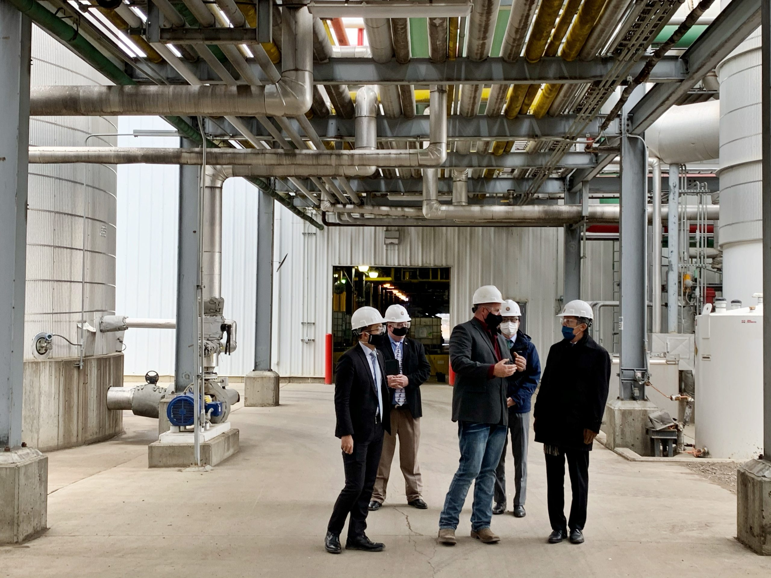Dustin Willett (center) gives a tour to Consul General Okada (right) at Red Trail Energy
